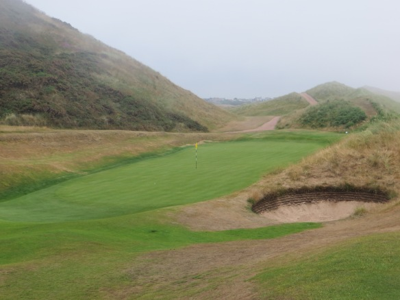 This sunken green lurks behind the dune on your approach into the Par 4 14th.
