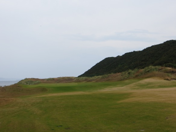 The back begins with holes framed by the dunes on the right and the sea on the left.